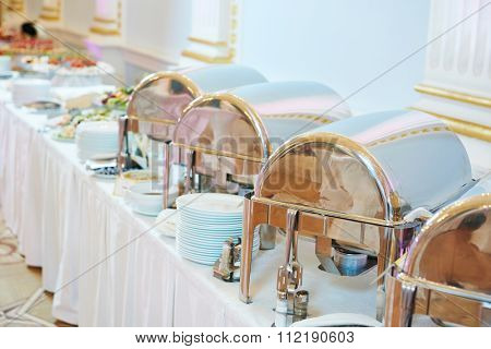 catering service. Metal buffet heated trays with food on tables at banquet event celebration
