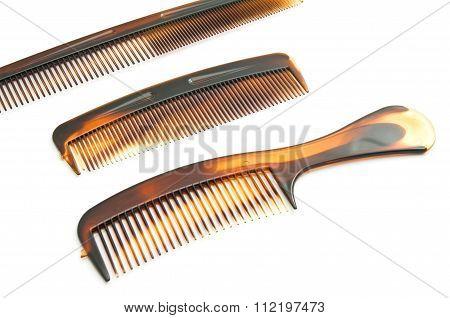 three brown hairbrush on white background closeup poster