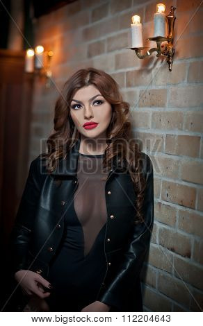 Charming brunette with black leather jacket against red bricks wall. Sexy gorgeous young woman