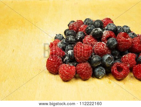 A Handful Of Frosted Highbush Blueberries And Raspberries On Old Wooden Board