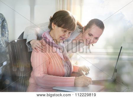 Younger woman helping an elderly person using laptop computer for internet search. Young and pension