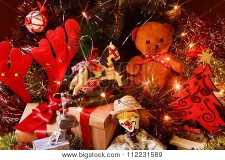 some gifts and some retro toys, such as a teddy bear, a horse or a marionette, under a christmas tree ornamented with lights, balls and tinsel
