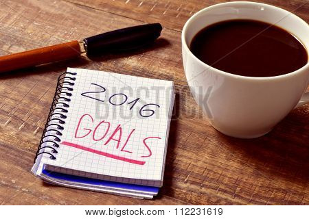 closeup of a notebook with the text 2016 goals written in it and a cup of coffee on a rustic wooden table