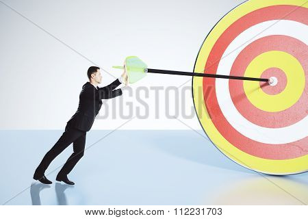Businessman Pushes Arrow Exactly In Bull's-eye Concept