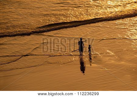 Woman And Child On Beach At Sunset.