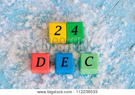 December 24 sign on color wooden cubes with snow and light blue background. Winter Christmas concept
