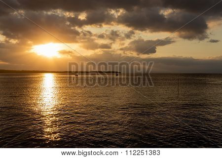 sunset on Bali sea Nusa Penida Island Toyapakeh Indonesia - boat with silhouette of Lembogan at evening with dramatic sky poster