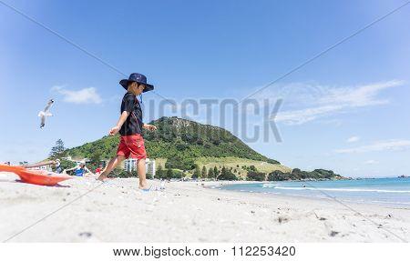 Boy In Sun Hat Walks Down Mount Maunganui Beach.