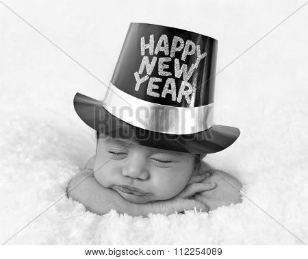 Newborn baby girl wearing a Happy New Year hat in black and white.