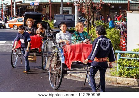TOKYO JAPAN - NOVEMBER 15 2015: Unidentified rickshaw drivers with passengers in Asukusa station nearby Sumida river