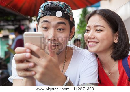 Asian Younger Man And Woman Watching On Smart Phone Use For People And Digital Technology ,wifi And