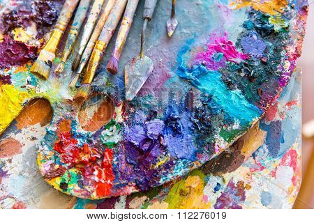 Closeup of art palette with bright colorful mixed paints, paintbrushed and palette knives