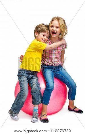 Little girl and boy sitting on pink ball