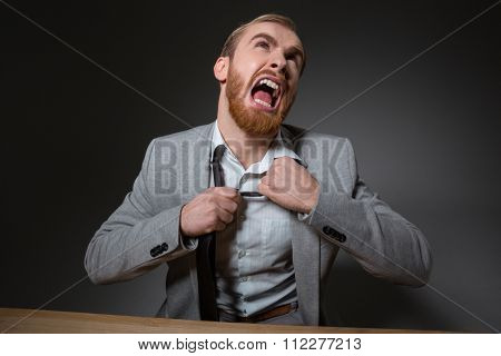 Portrait of mad screaming businessmen with beard in grey suit over grey background