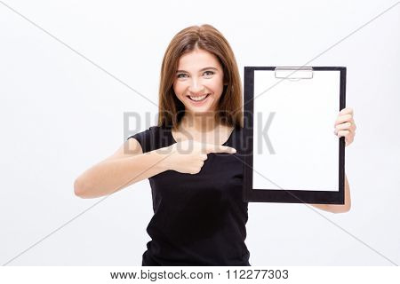 Cheerful attractive young woman showing blank clipboard and pointing on it over white background