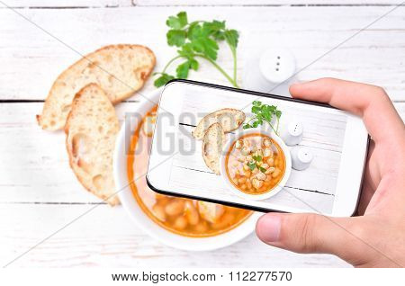 Hands taking photo bean soup with smartphone.