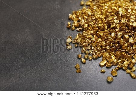 A pile of Gold nugget grains, on cement background