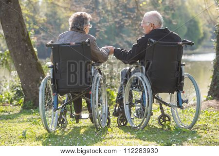 Elderly couple in wheelchairs, holding hands