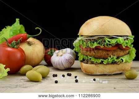 Big buttermilk chiken burger with ingredients on wooden table, dark background.