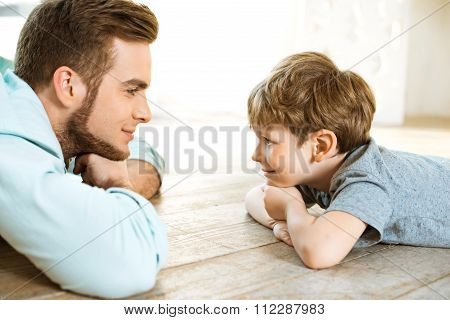 Little boy and his father on wooden floor