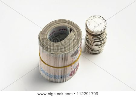 Rolled Hundred dirham bills along with stack of coins. 'Profit on investment' - an idea.