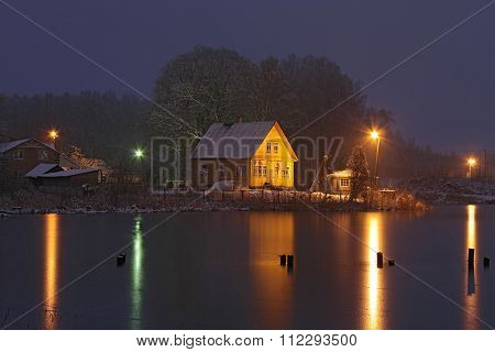 Yellow House On  Frozen Lake At Night