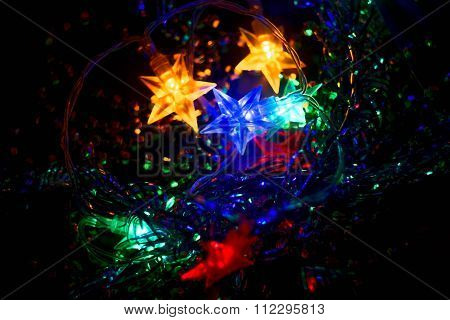 Defocused Xmass Garland with stars. Holiday Glowing Background. Shallow DOF