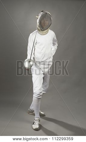 Full length of a foil fencer on gray background.