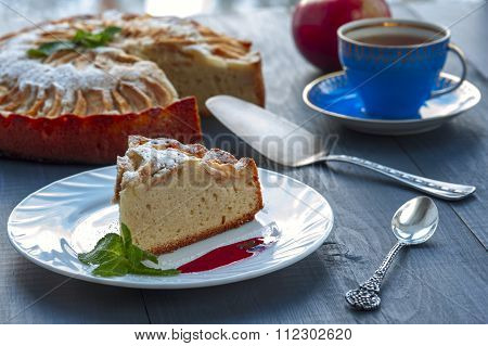 Piece of apple pie on plate with jam, tea cup