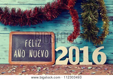 tinsel of different colors and a chalkboard with the text feliz ano nuevo, happy new year in spanish, and white numbers forming the number 2016, on a rustic wooden surface sprinkled with confetti