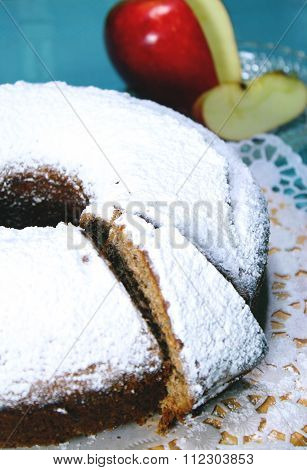 apple cake topped with icing sugar and apple