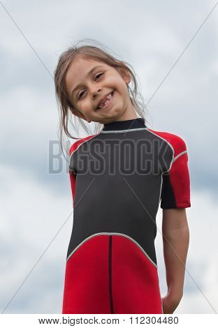 Portrait Of Little Girl With A Missing Tooth Smiling Outside