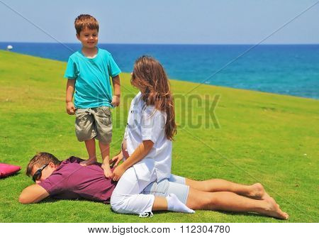 Beautiful four year old boy having fun playing with his aunt and uncle on a green grassy lawn. A young pregnant woman smiling