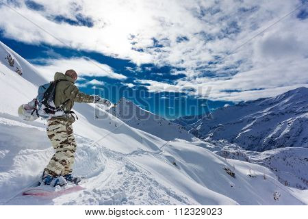 Snowboarder goes downhill over a snowy mountain landscape. Gressoney, Val d'Aosta, Italy.