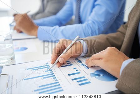 Businesswoman pointing at graphs and charts at the table