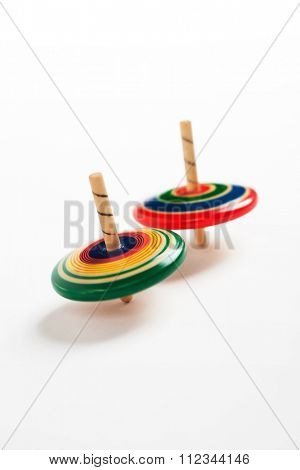 Two wooden top spinning, isolated on natural white background. Blurred effect of spinning, shallow depth of field.