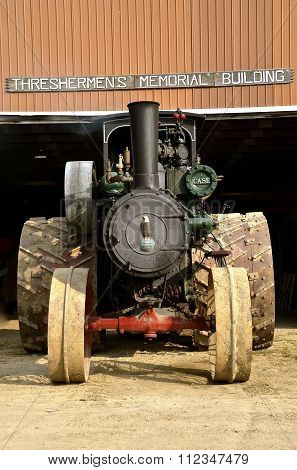 Steam engine parked in front of a thresher building
