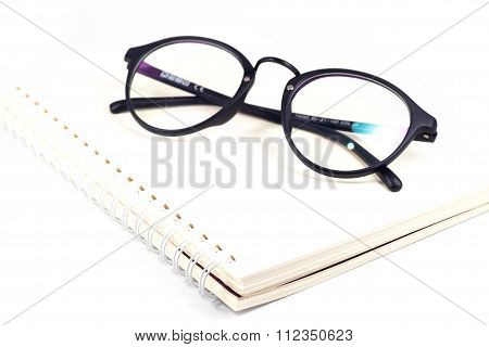 Blank Spiral Notebook And Eyeglasses Isolated On White Background