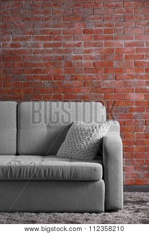 Comfortable sofa on brick wall background