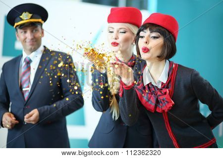 MOSCOW - JUL 09, 2015: Two flight attendants in red hats blow away gold sequins with palms at DME RUNVAY in Domodedovo