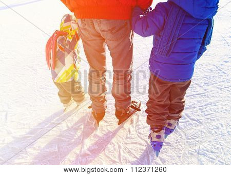 father with two kids skating in winter