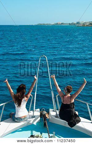 Twee vrouwen op jacht zitplaatsen op stern in blauwe zee