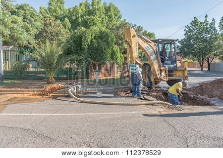 Municipal Workers Repairing Leaking Water Pipe