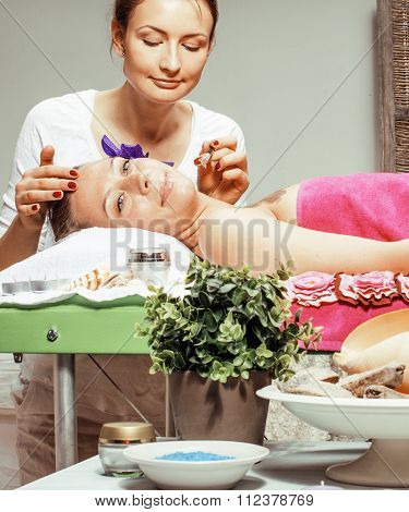 stock photo attractive lady getting spa treatment in salon, massage doctor smiling