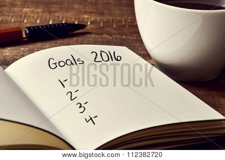 closeup of a notebook with a blank list of goals for 2016 and a cup of coffee on a rustic wooden table