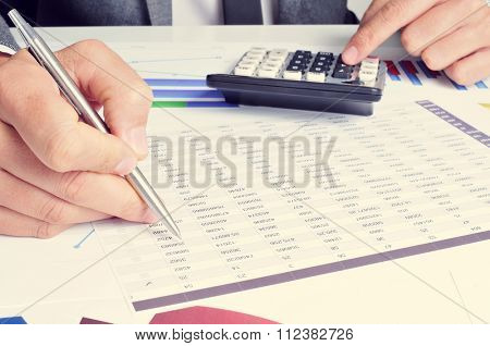 closeup of a young caucasian businessman checking accounts with a calculator in his office