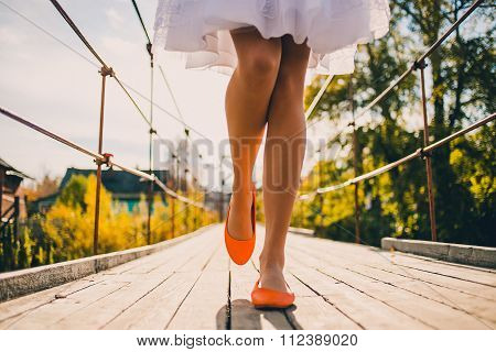 Unusual wedding shoes on the feet of the bride, bright orange, walk in the park