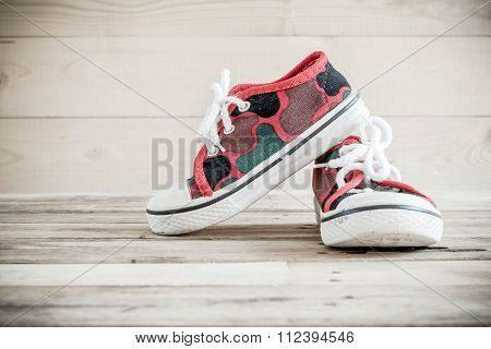 Old Baby Shoes On Wooden Background.