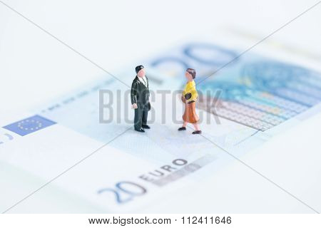 Miniature Man And Woman On Euro Banknotes