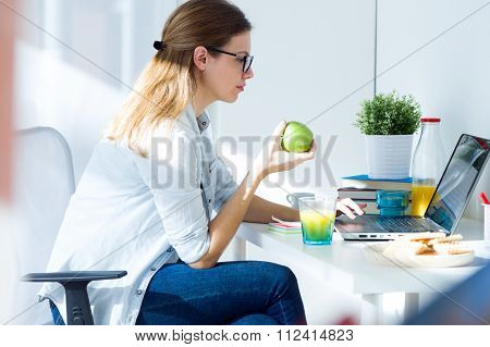 Pretty Young Woman Eating An Apple And Working At Home.